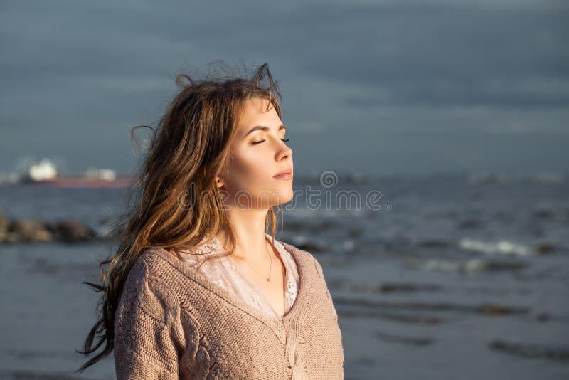 Nätt flicka som kopplar av på havkusten, romantisk stående royaltyfri foto