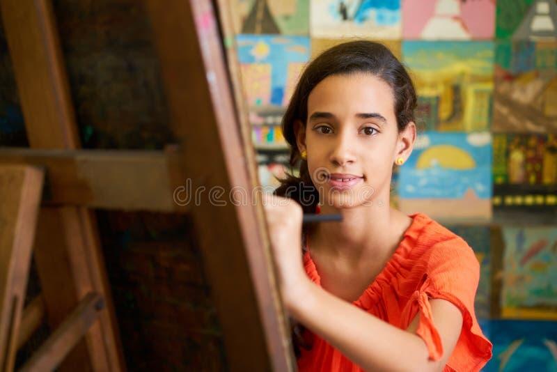 Nätt flicka som ler på den kvinnliga studenten In Art School för kamera arkivfoton