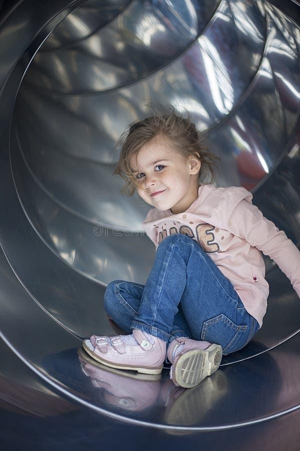Nätt flicka som poserar på en glidbana i lekplatsen arkivbilder