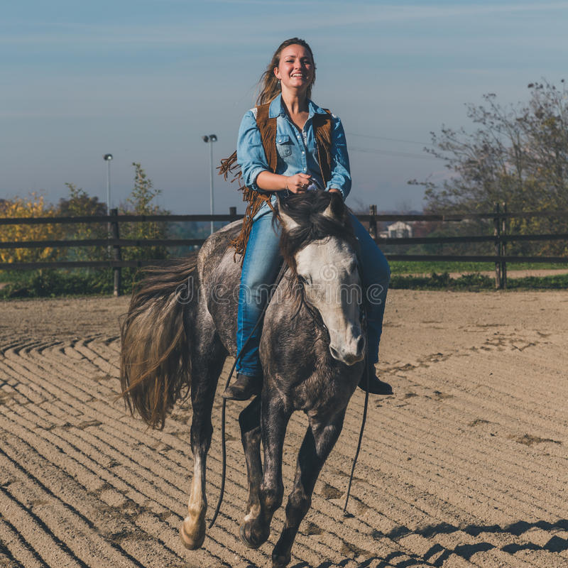 Nätt flicka som rider hennes gråa häst arkivbilder