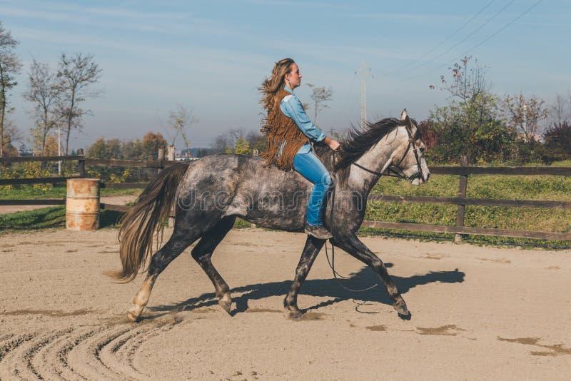 Nätt flicka som rider hennes gråa häst royaltyfri foto