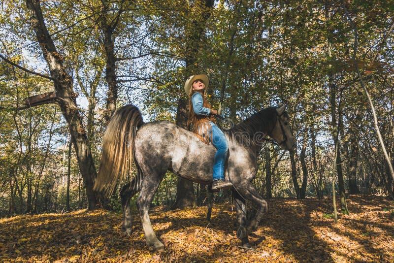 Nätt flicka som rider hennes gråa häst royaltyfria foton