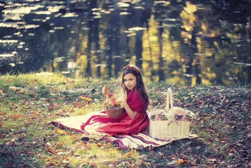 Nätt flicka som rymmer den lilla korgen royaltyfria foton