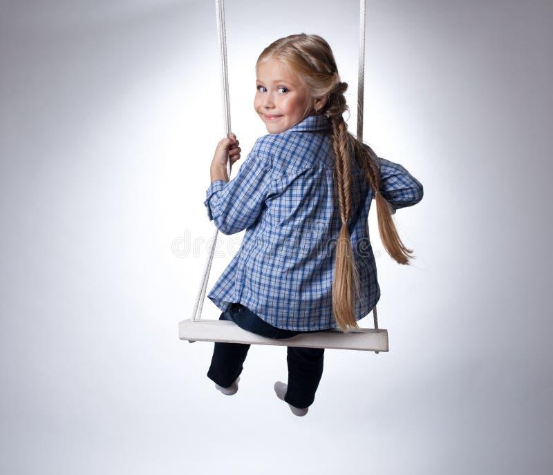 Nätt flicka som sitter på swing royaltyfri bild