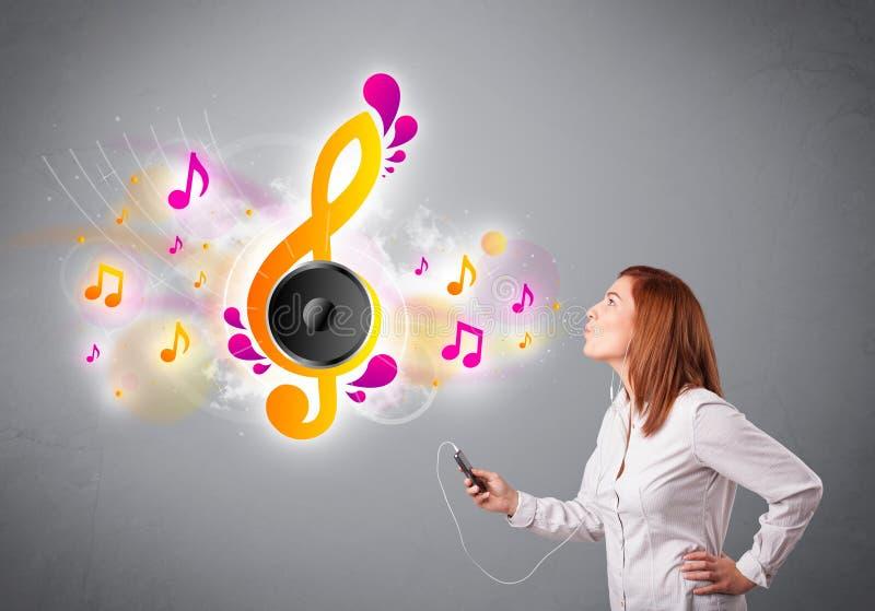 Nätt flicka som sjunger och lyssnar till musik med musikaliska anmärkningar royaltyfria foton