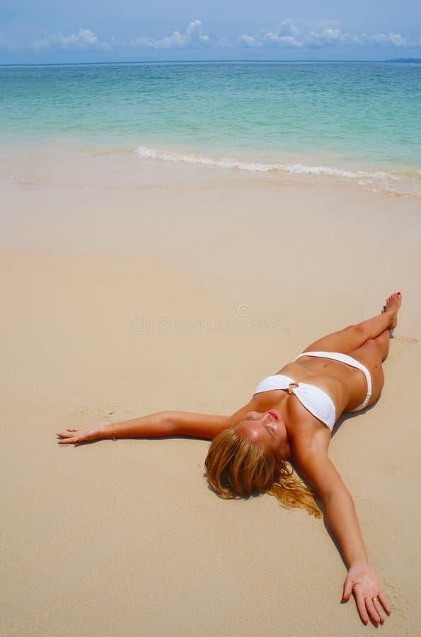 Nätt flicka som solbadar på stranden royaltyfri fotografi