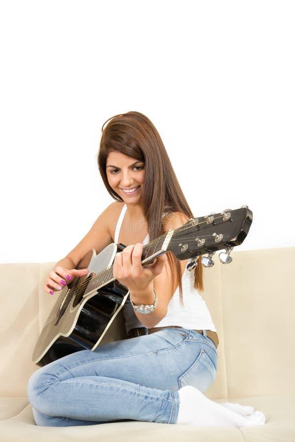 Nätt flicka som spelar gitarren på soffan arkivfoton