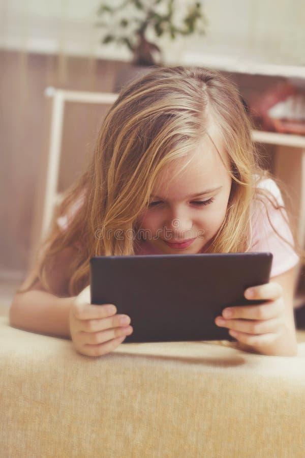 Nätt flicka som spelar i minnestavlan hemma, teknologibegrepp royaltyfria bilder
