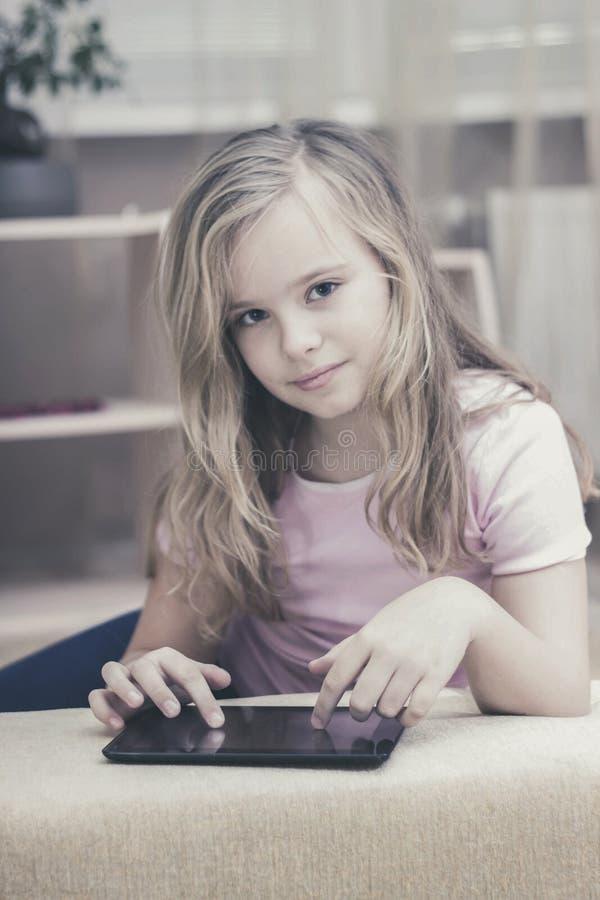 Nätt flicka som spelar i minnestavlan hemma, teknologibegrepp royaltyfri bild