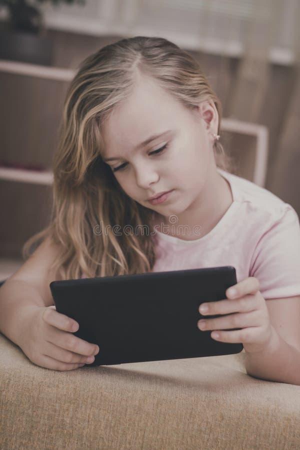 Nätt flicka som spelar i minnestavlan hemma, teknologibegrepp royaltyfri foto