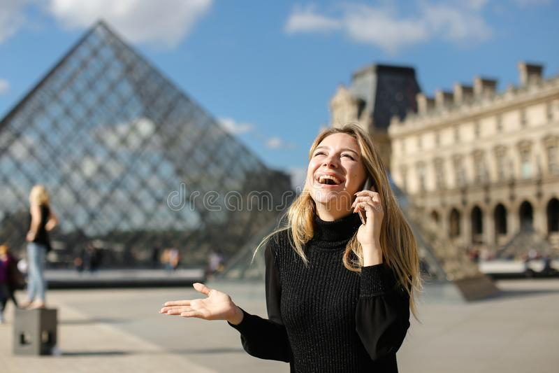Nätt flicka som står near Louvre och glass pyramind i svart klänning i Paris som talar vid smartphonen royaltyfria bilder