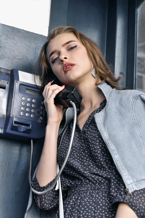 Nätt flicka som talar languidly på en löntelefon fotografering för bildbyråer