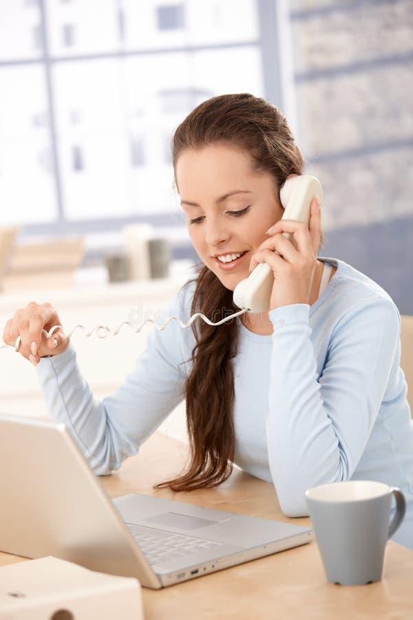 Nätt flicka som talar på telefonen genom att använda bärbara datorn hemma arkivbilder