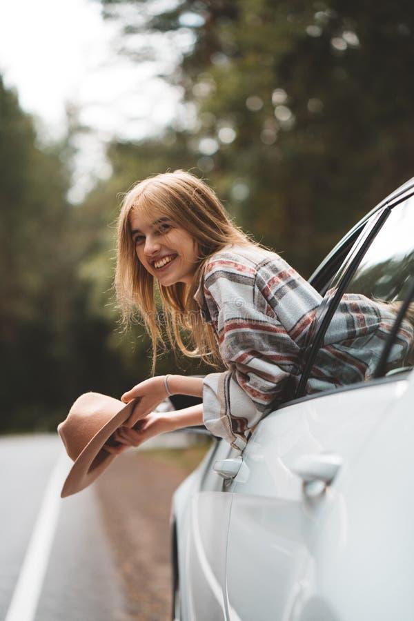 Nätt flickahipster som tycker om landsvägen arkivbild