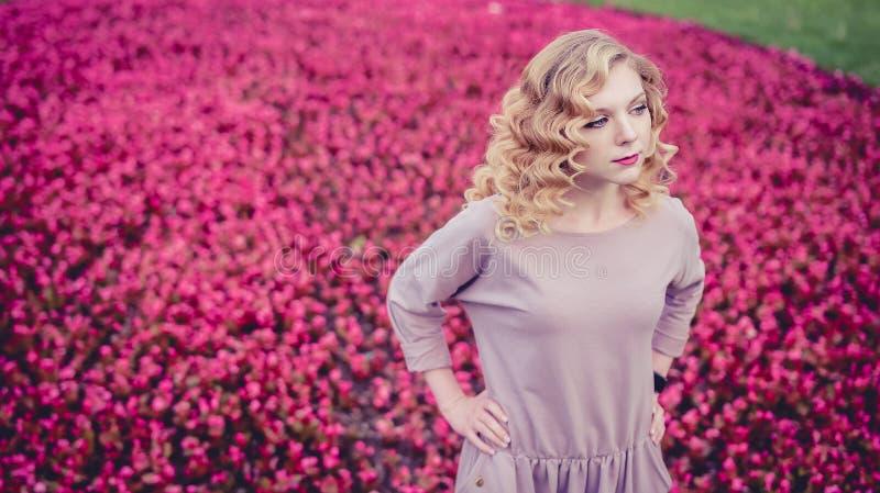 Nätt flickamodellanseende på en blommabakgrund royaltyfri fotografi
