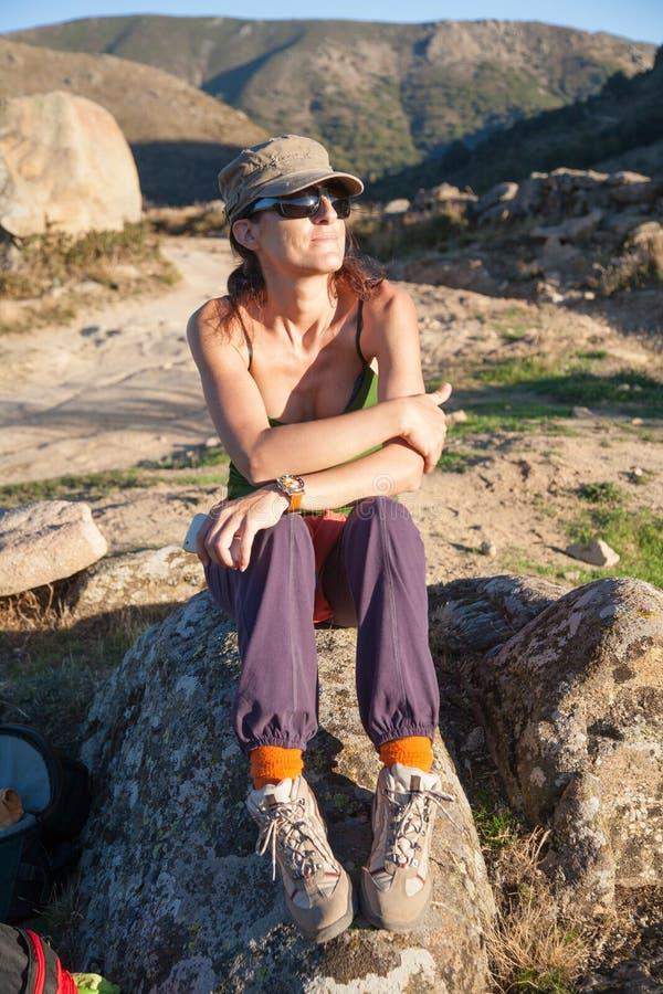 Nätt fotvandrarekvinnasammanträde vaggar på fotografering för bildbyråer