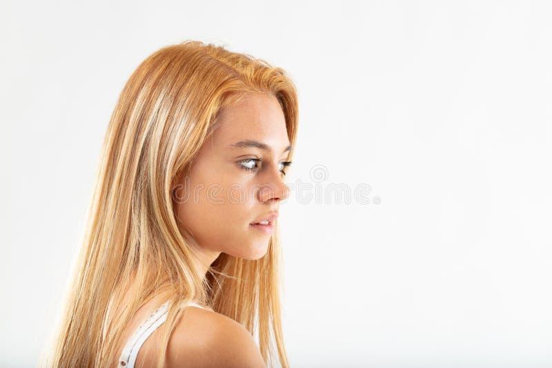 Nätt fundersam ung kvinna som åt sidan kastar en blick royaltyfri bild