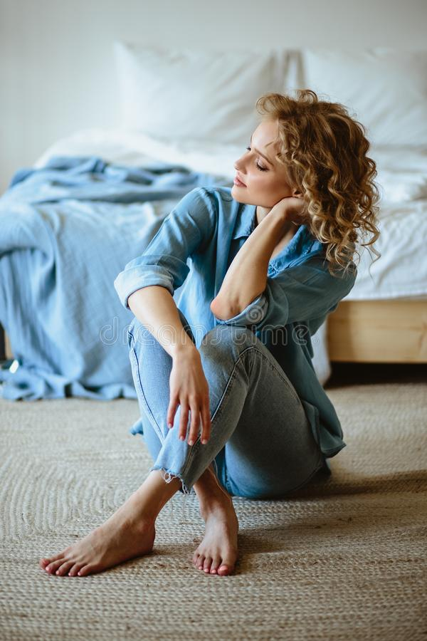 Nätt gladlynt blond ung kvinna med lockigt hår och charmaleende som vilar i hennes hem arkivbild
