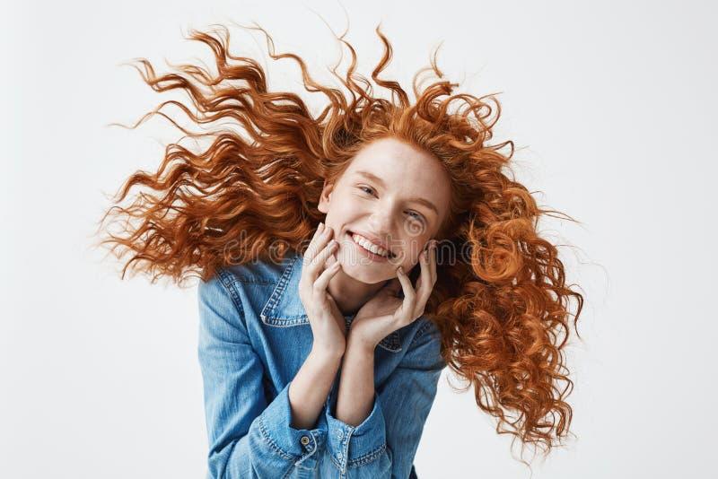 Nätt gladlynt rödhårig manflicka med att flyga lockigt hår som ler att skratta se kameran över vit bakgrund royaltyfri foto