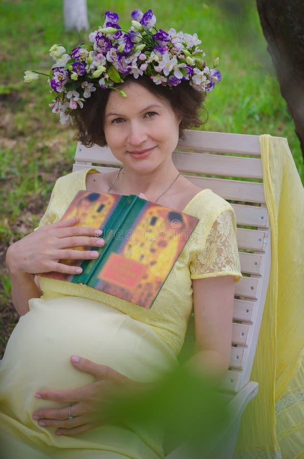 Nätt gravid kvinna i en gul klänning och en krans av blommor arkivfoton