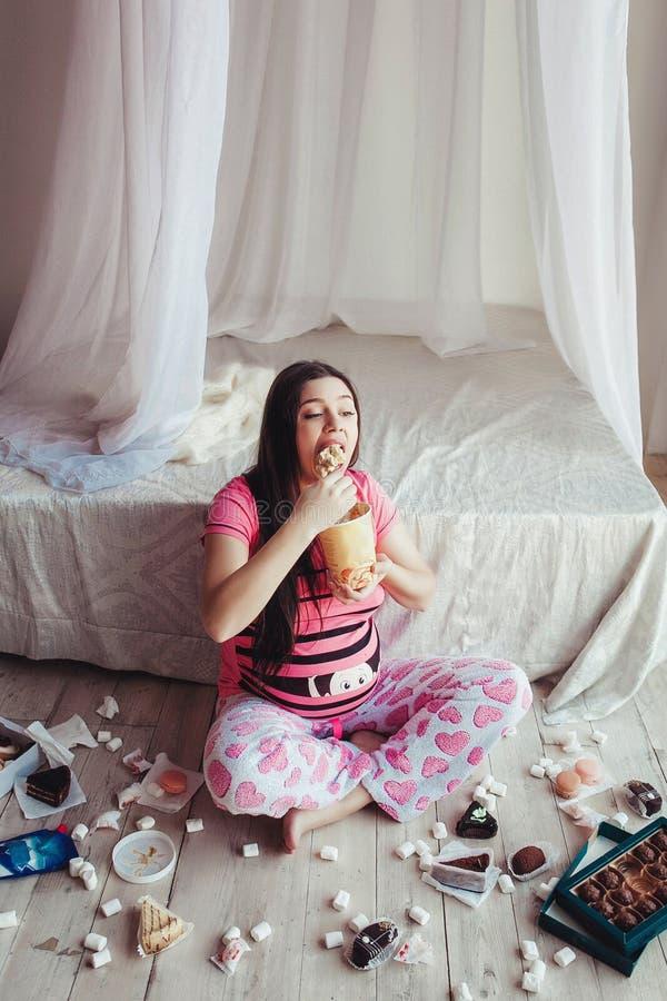 Nätt gullig gravid kvinna som äter glass fotografering för bildbyråer