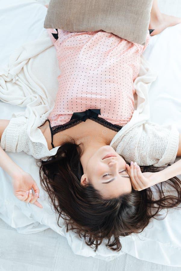 Nätt gullig ung kvinna som sover i säng royaltyfri foto