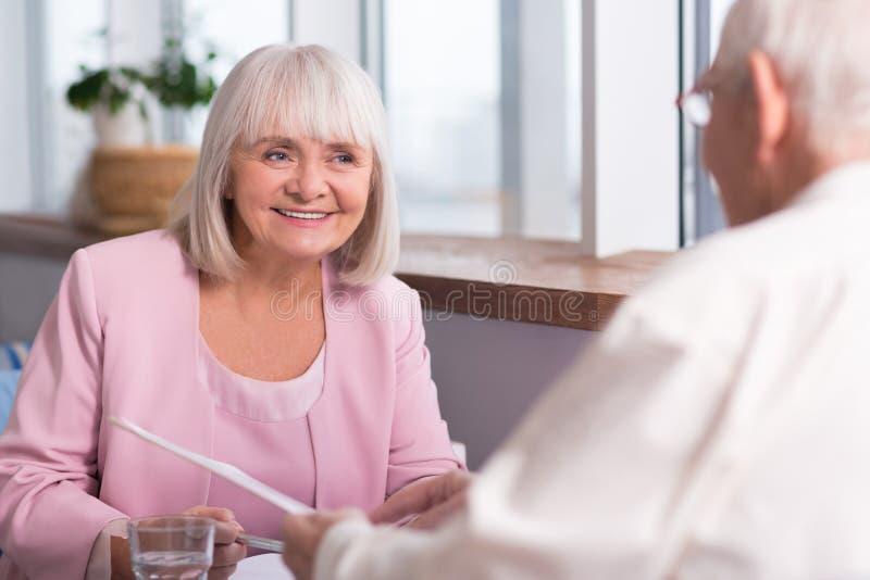 Nätt hög affärskvinna som ler på hennes kollega arkivbild