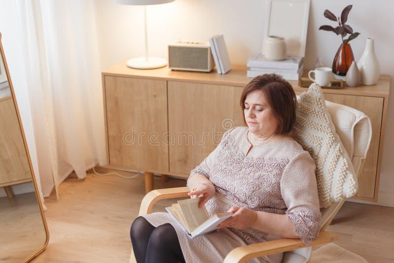Nätt hög kvinna som tillbaka sitter på fåtöljen med att intressera boken royaltyfria bilder