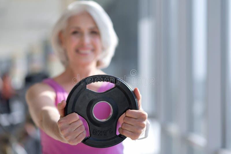 Nätt hög le hållande sportutrustning för kvinna royaltyfri foto