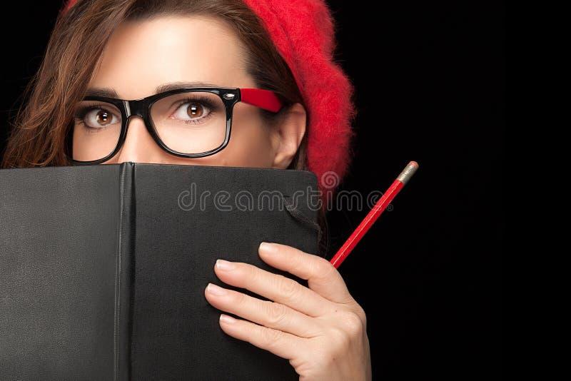 Nätt högskolaflicka som täcker hennes framsida med den svarta anteckningsboken arkivbilder