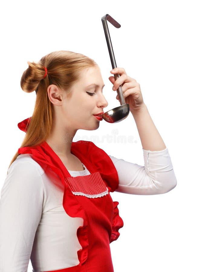 Nätt hemmafru i rött förkläde med roliga hästsvansar som smakar mål royaltyfri foto