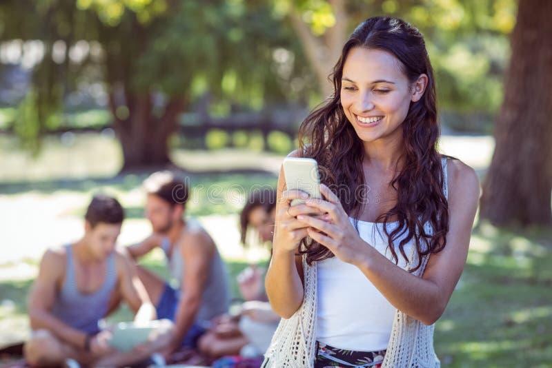 Nätt hipster som använder hennes smartphone royaltyfria foton