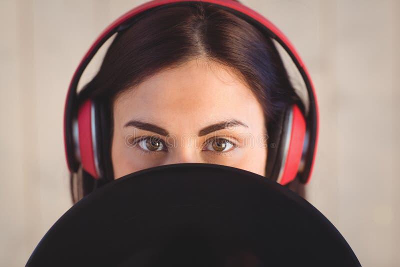 Nätt hipster som lyssnar till hållande vinyl för musik royaltyfria bilder