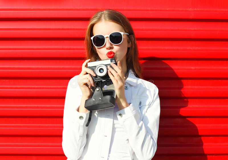 Nätt kall kvinna med den retro kameran över rött arkivbilder