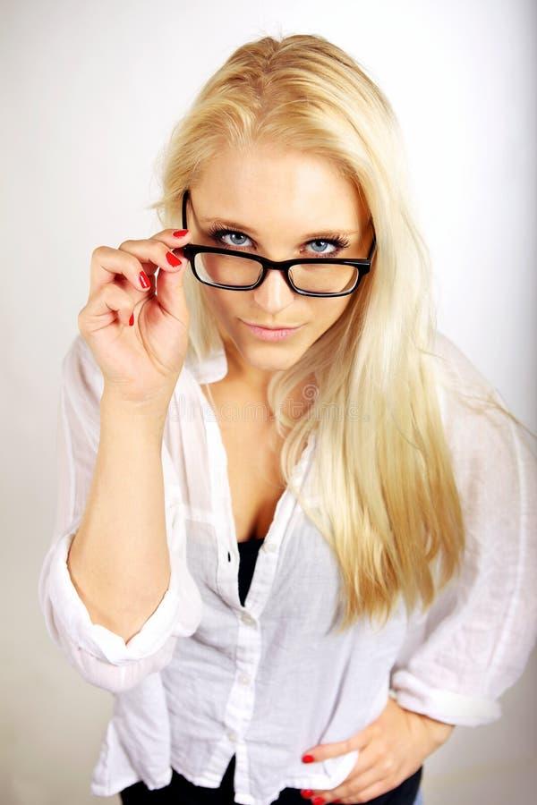 Nätt karriärkvinna som justerar henne glasögon royaltyfria foton