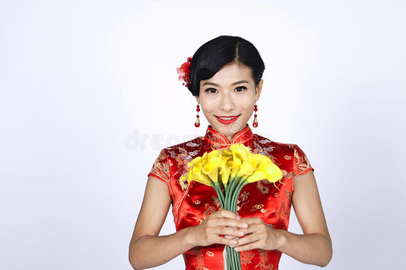 Download Nätt Kinesisk Ung Kvinna Som Rymmer En Grupp Av Gula Påskliljor Arkivfoto - Bild av klänning, fira: 78731254