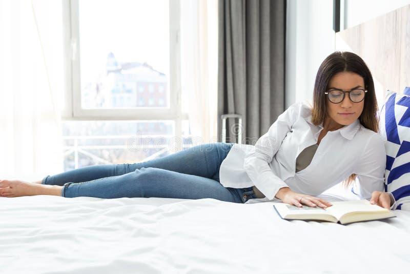 Nätt koncentrerad ung kvinna som läser en bok, medan ligga på säng i hotellrum royaltyfri fotografi