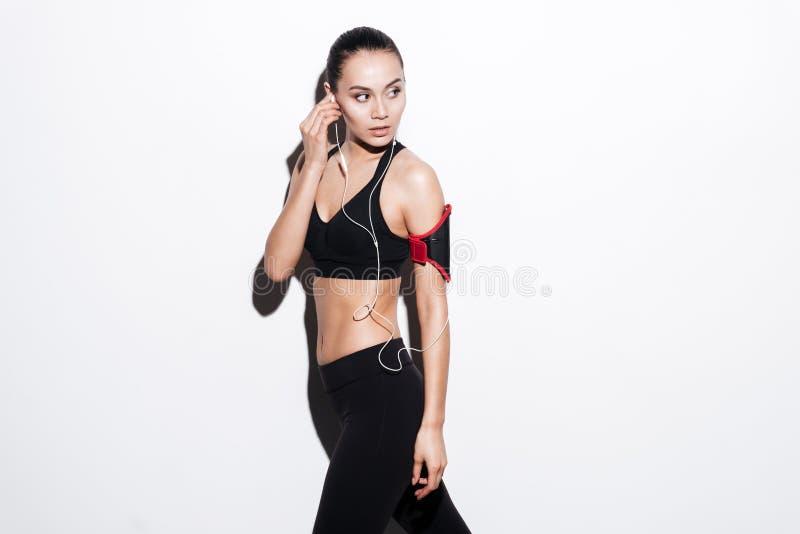 Nätt konditionkvinna med armbindeln som går och lyssnar till musik royaltyfria foton