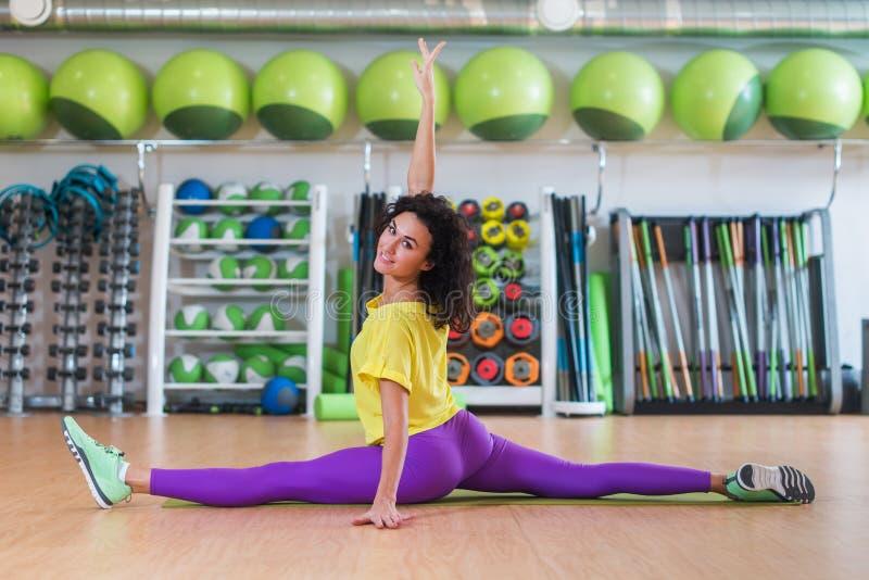 Nätt konditionmodell i sportswearen som gör framdelen som delas i idrottshall och att sträcka henne ben och att se kameran och at arkivfoton