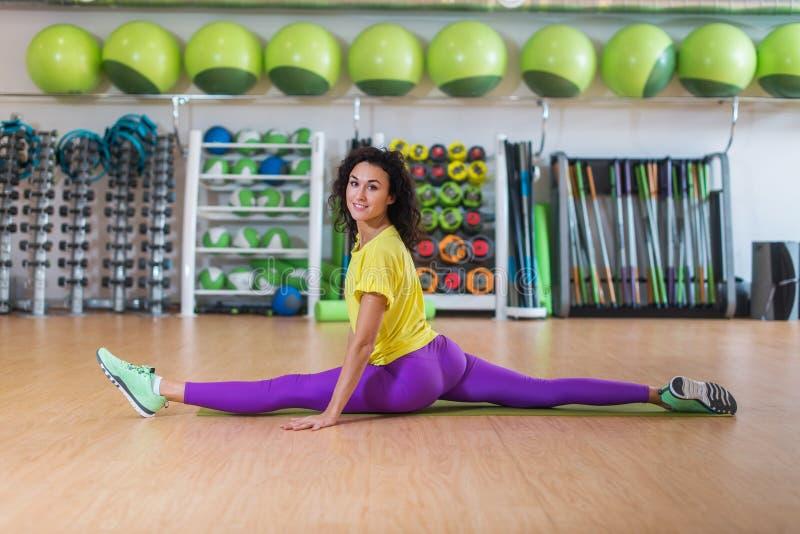 Nätt konditionmodell i sportswearen som gör framdelen som delas i idrottshall och att sträcka henne ben och att se kameran och at arkivbilder