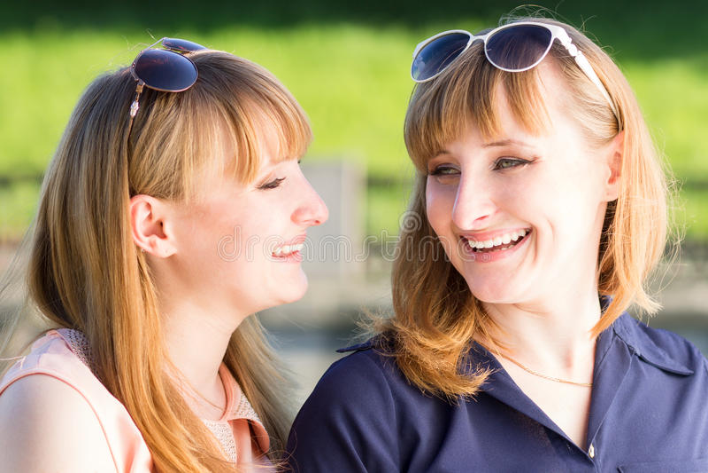 Nätt kopplar samman flickor som har gyckel på utomhus- sommar, parkerar royaltyfri fotografi