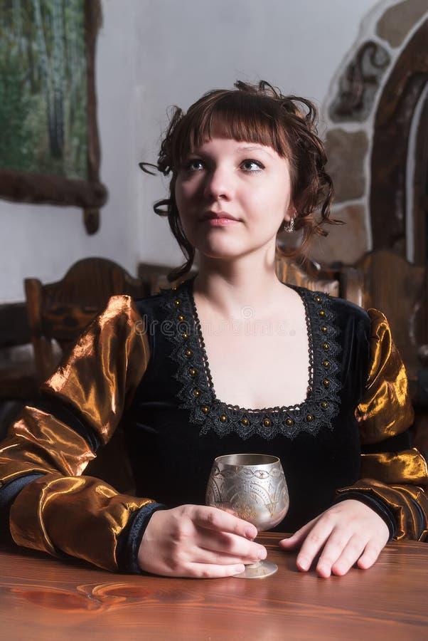 Nätt kvinna en fåtölj och med vinexponeringsglas royaltyfri bild
