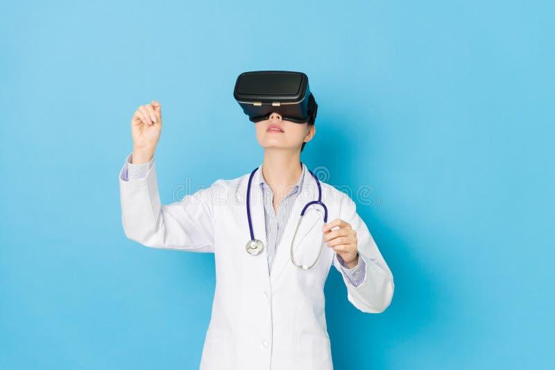 Nätt kvinna för sjukhusdoktor som bär VR-teknologi arkivbild