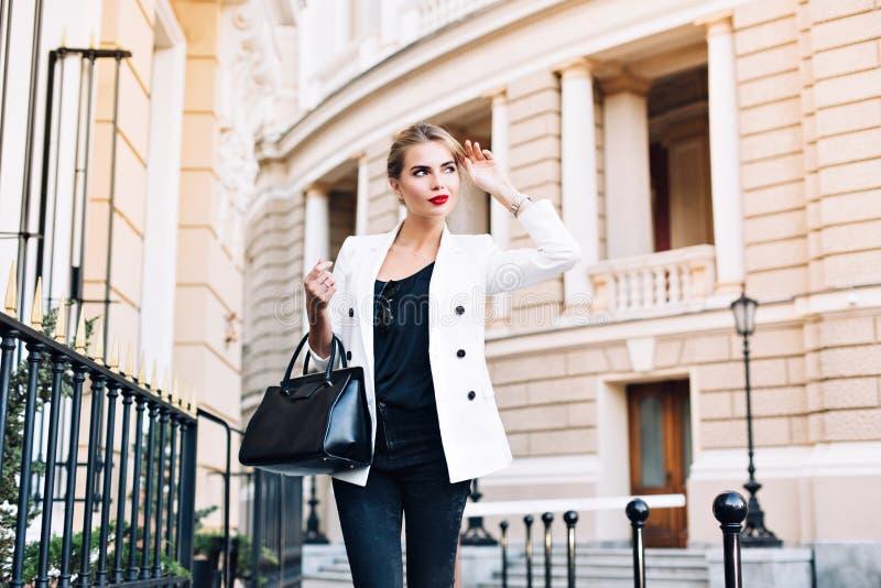 Nätt kvinna för stående i det vita omslaget som går på gatan r arkivfoto