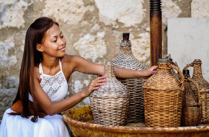 Nätt kvinna i den etniska medelhavs- folk traditionella dräkten som rymmer en rottingolivoljatillbringare Gästfrihet- och person  arkivbilder