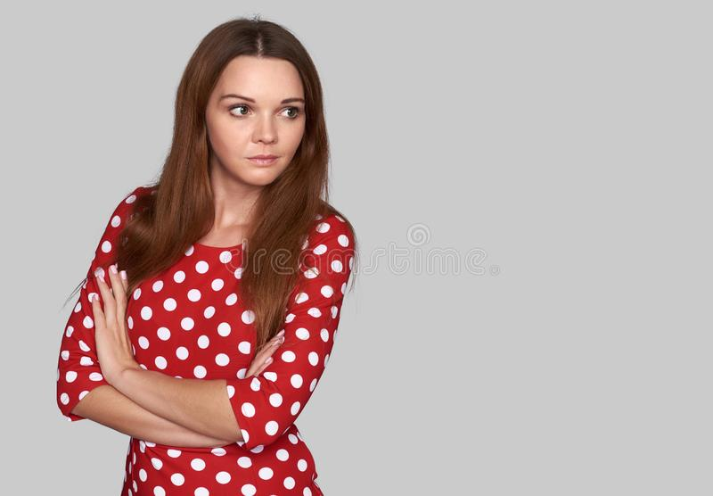 Nätt kvinna i den tillfälliga röda klänningen som åt sidan ser royaltyfri bild