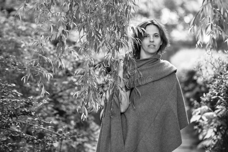 Nätt kvinna i en poncho bland lövverket i parkera, svartvitt fotografi arkivbild