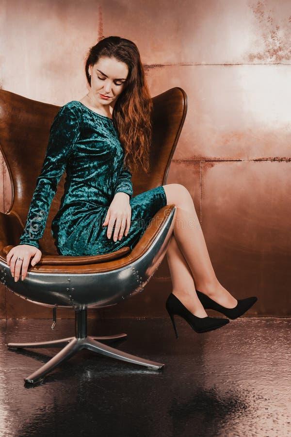 Nätt kvinna i en sammetklänning som sitter i en läderstol, luxu royaltyfri foto