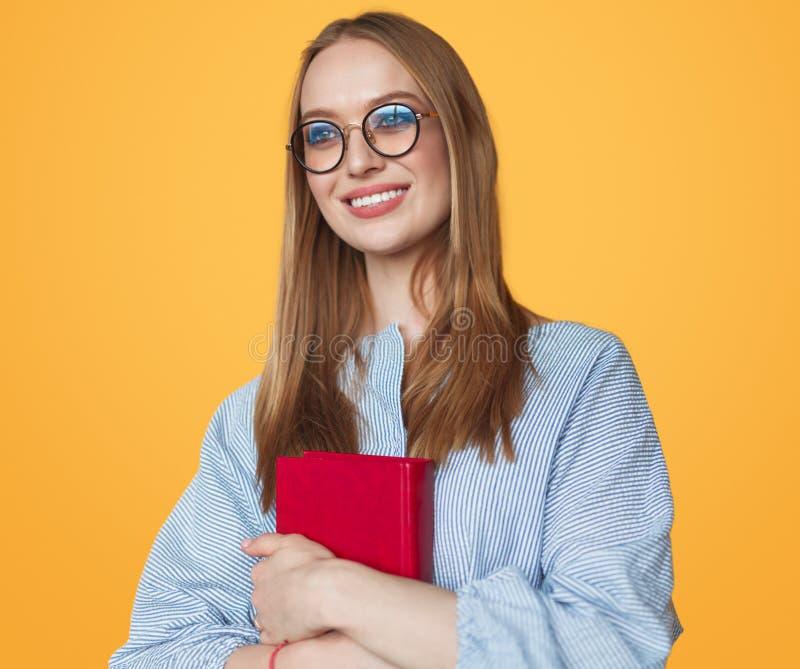 Nätt kvinna i exponeringsglas som rymmer boken royaltyfri fotografi