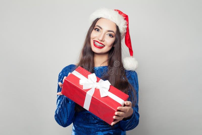 Nätt kvinna i hänglsen som rymmer jul eller gåvan och att le för nytt år royaltyfria foton